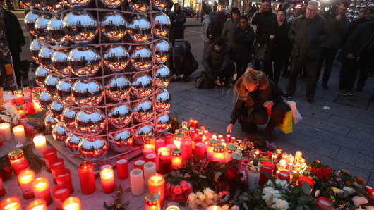 Mourners light candles at the entrance to a Christmas market in Berlin, Germany, close to where a lorry ploughed through crowds and killed 12 people on December 19, 2016.