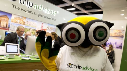 A mascot of TripAdvisor is seen at its display at a trade fair.