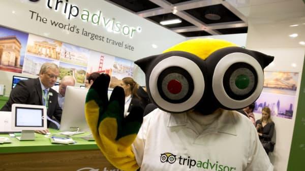 A mascot of TripAdvisor is seen at its display at a trade fair.