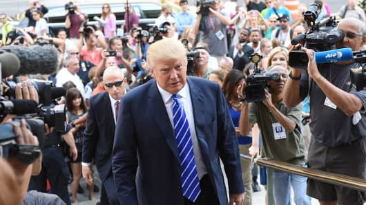 Donald Trump ascends steps of Manhattan Supreme Court surrounded by press on August 08, 2015.