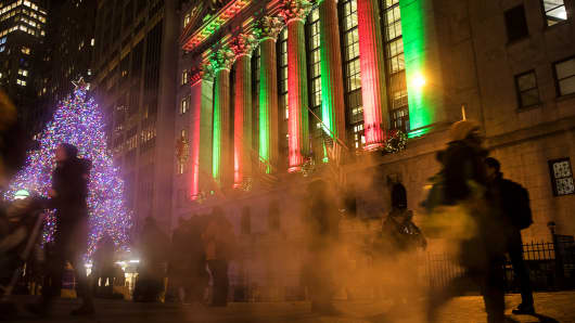 Pedestrians pass by the New York Stock Exchange.