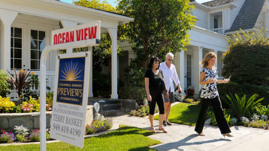A realtor, at right, shows prospective buyers a property in Newport Beach, California.