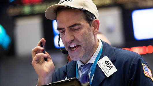A trader wearing a Dow 20,000 hat works on the floor of the New York Stock Exchange.