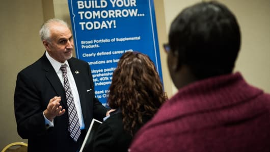 An insurance agency representative speaks with job seekers during a Choice Career Fair in New York.