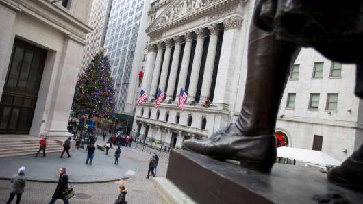 Pedestrians walk along Wall Street as a Christmas tree stands in front of the New York Stock Exchange.