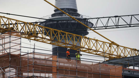Workers stand near a crane at a construction site in front of the Sky Tower in Auckland, New Zealand, on Friday, Dec. 9, 2016.