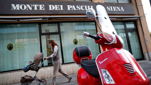 A pedestrian pushes a baby stroller past a red Vespa scooter outside a Banca Monte Dei Paschi Di Siena SpA bank in Pescara, Italy.