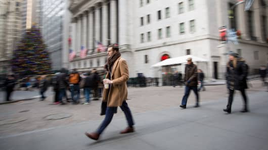 Pedestrians walk along Wall Street in front of the New York Stock Exchange, Dec. 21, 2016.