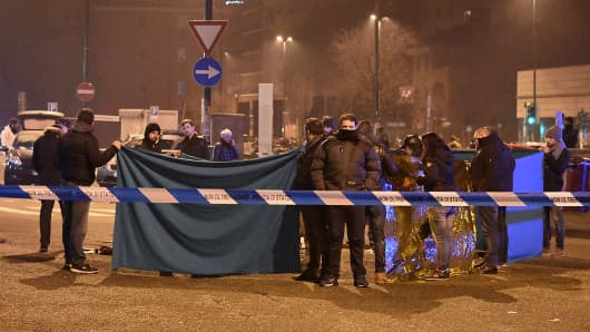 Italian police and forensics experts gather around the body of suspected Berlin truck attacker Anis Amri after he was shot dead in Milan on December 23, 2016.