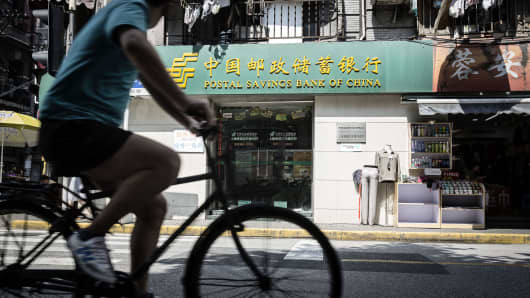 A cyclist rides past a Postal Savings Bank of China branch in Shanghai.