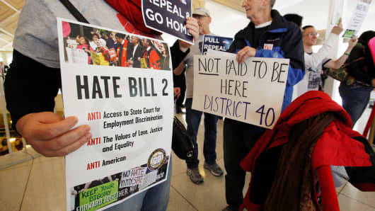 Opponents of North Carolina's HB2 law, limiting bathroom access for transgender people, protest in the gallery above the state's House of Representatives chamber in Raleigh, North Carolina, on December 21, 2016.