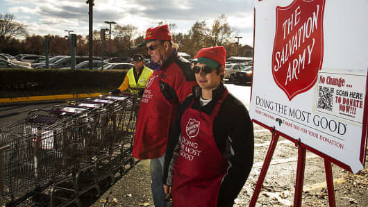 Salvation Army bell ringer volunteers William Schmidt (L), who is on his 20th year volunteering, and his grandson Bubba Wellens (R) ring their bells looking for a concession into a kettle outward a Giant grocery store Nov 24, 2012, in Clifton, Virgina.
