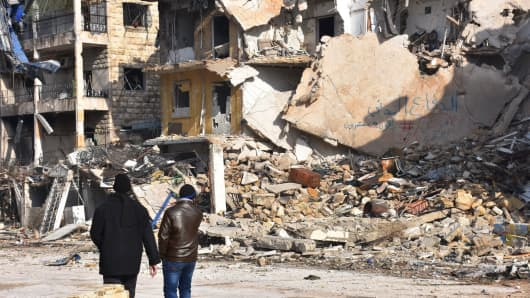 Syrians walk through the former rebel-held Zebdiye district in the northern Syrian city of Aleppo on December 23, 2016.