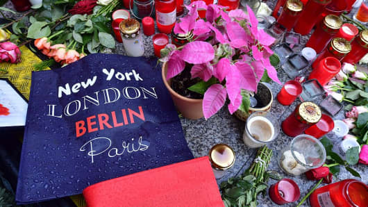 Candles, flowers and individual messages are placed at a makeshift memorial for the victims of the Christmas market attack near the Kaiser-Wilhelm-Gedaechtniskirche (Kaiser Wilhelm Memorial Church) in Berlin on December 24, 2016.