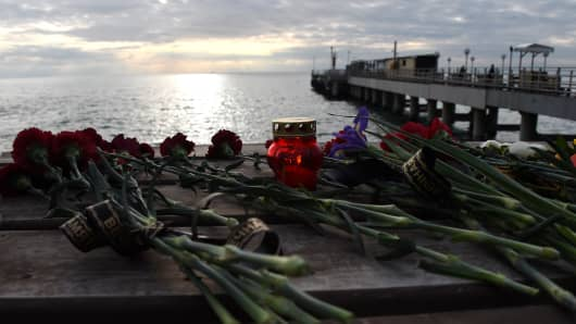 Flowers are left along the walk way running along the Black Sea in the coastal city of Sochi, on December 26, 2016, a day after a military plane crashed out at sea.