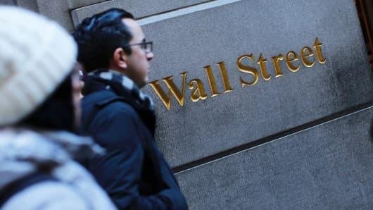 Pedestrians walk outside the New York Stock Exchange.