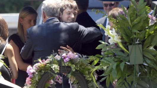 John Ramsey (L) hugs his son Burke at the grave of JonBenet Ramsey after graveside service for his wife Patsy Ramsey June 29, 2006 in Marietta, Georgia.