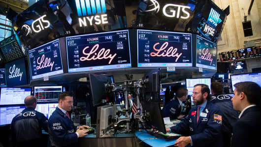 Traders work beneath monitors displaying Eli Lilly & Co. signage on the floor of the New York Stock Exchange (NYSE) in New York, U.S., on Monday, May 23, 2016.