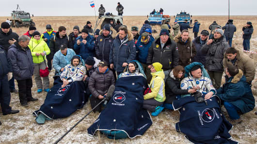 Russian cosmonauts Mikhail Kornienko, left, Sergey Volkov of Roscosmos, center, and Expedition 46 Commander Scott Kelly of NASA, rest in a chairs outside of the Soyuz TMA-18M spacecraft just minutes after they landed in a remote area on March 2, 2016 near the town of Zhezkazgan, Kazakhstan.