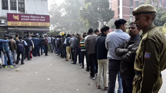 People stand in a long queue to dispense currency at a working ATM, on December 10, 2016 in New Delhi, India.