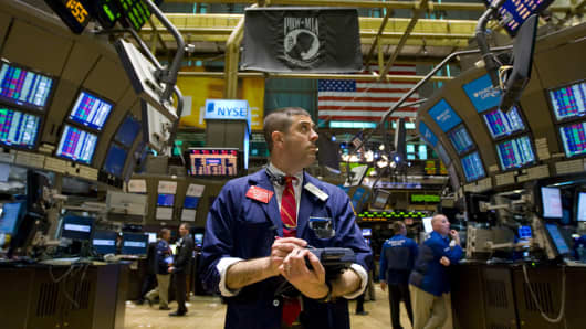 A trader looks up at a monitor while working on the floor of the New York Stock Exchange