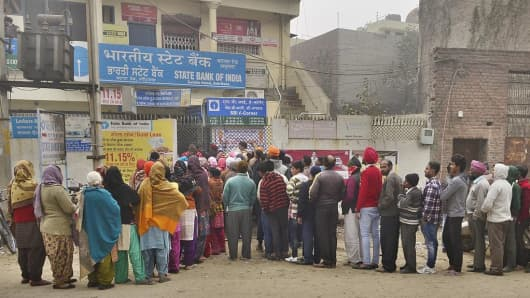 People queue outside a State Bank of India branch at Batala Road on December 29, 2016, in Amritsar, India.