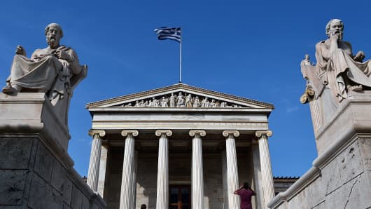 Tourists take pictures in front of the Athens Academy adorned with sculptures depicting ancient Greek philosophers , Plato (L) and Socrates (R) on June 10, 2016.