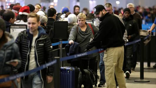 Travelers wait in line at O'Hare International Airport on December 23, 2016.