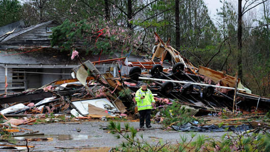 A utility worker stands in front of the site on Alabama Highway 71where three people were killed and one critically injured when their mobile home flipped over as an early-morning tornado tore through the small Sand Mountain town on November 30, 2016 in Rosalie, Alabama