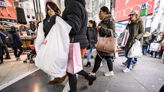 Shoppers walk in front of a H&M store in New York City.