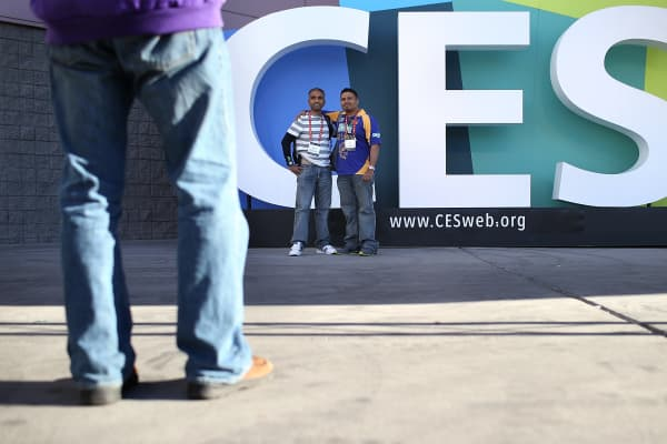 Attendees take their photo in front of a sign as they arrive at the International CES at the Las Vegas Convention Center.