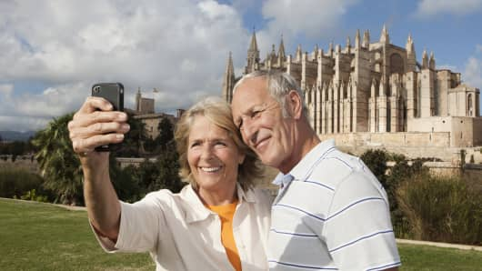 Couple smiling taking picture with Cathedral Santa Maria, in Mallarca, Spain.