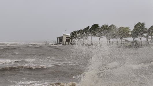 A house is seen as strong waves caused by Cyclone Evan wash a beach in Queen Elizabeth Drive, in Suva in this handout picture taken December 17, 2012.