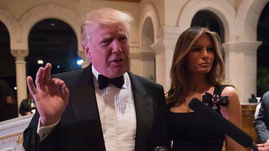 U.S. President-elect Donald Trump answers questions from reporters accompanied by his wife Melania for a New Year's Eve party December 31, 2016 at Mar-a-Lago in Palm Beach, Florida.