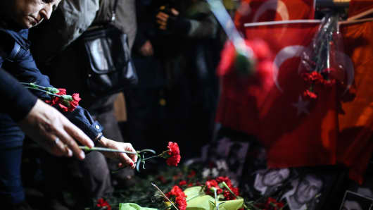 People leave carnations at site as they take part in a protest against Istanbul nightclub terror attack in Istanbul, Turkey.