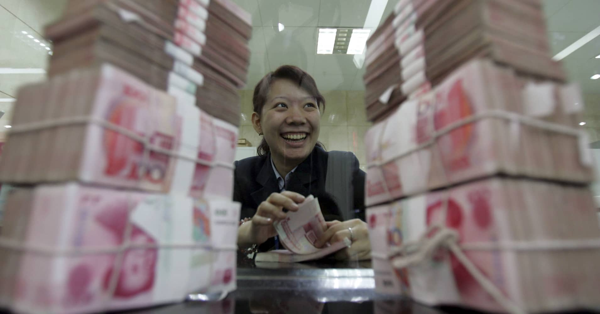 A clerk counts stacks of Chinese yuan at a bank in Beijing, China.