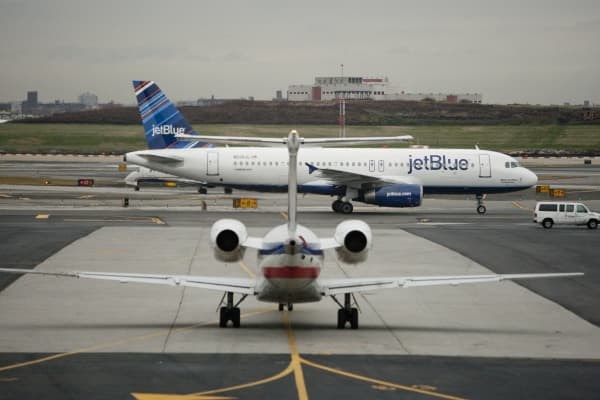 A JetBlue Airways Corp. plane taxis past an American Airlines plane at LaGuardia Airport in New York.