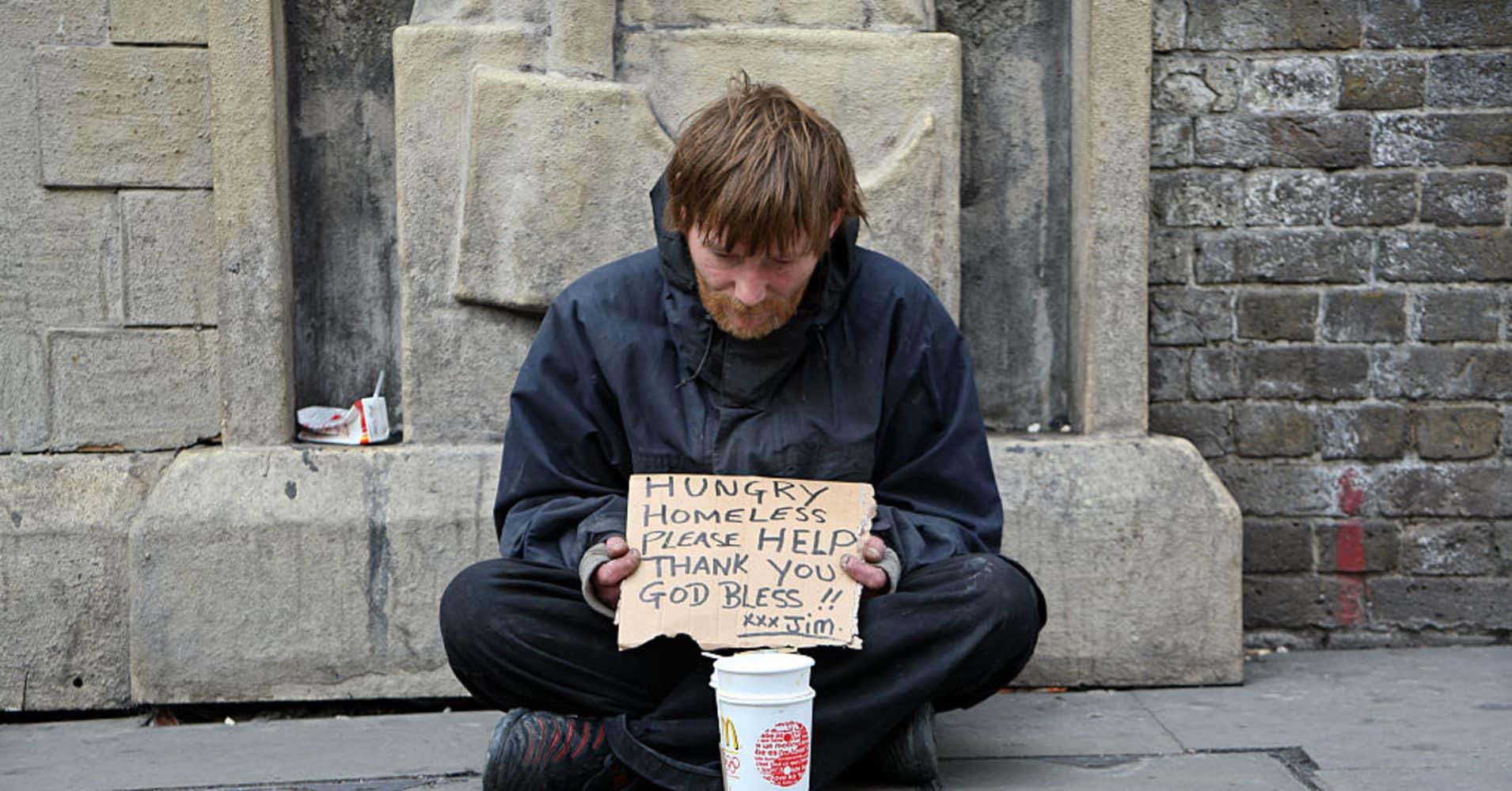 A homeless man begging for money.