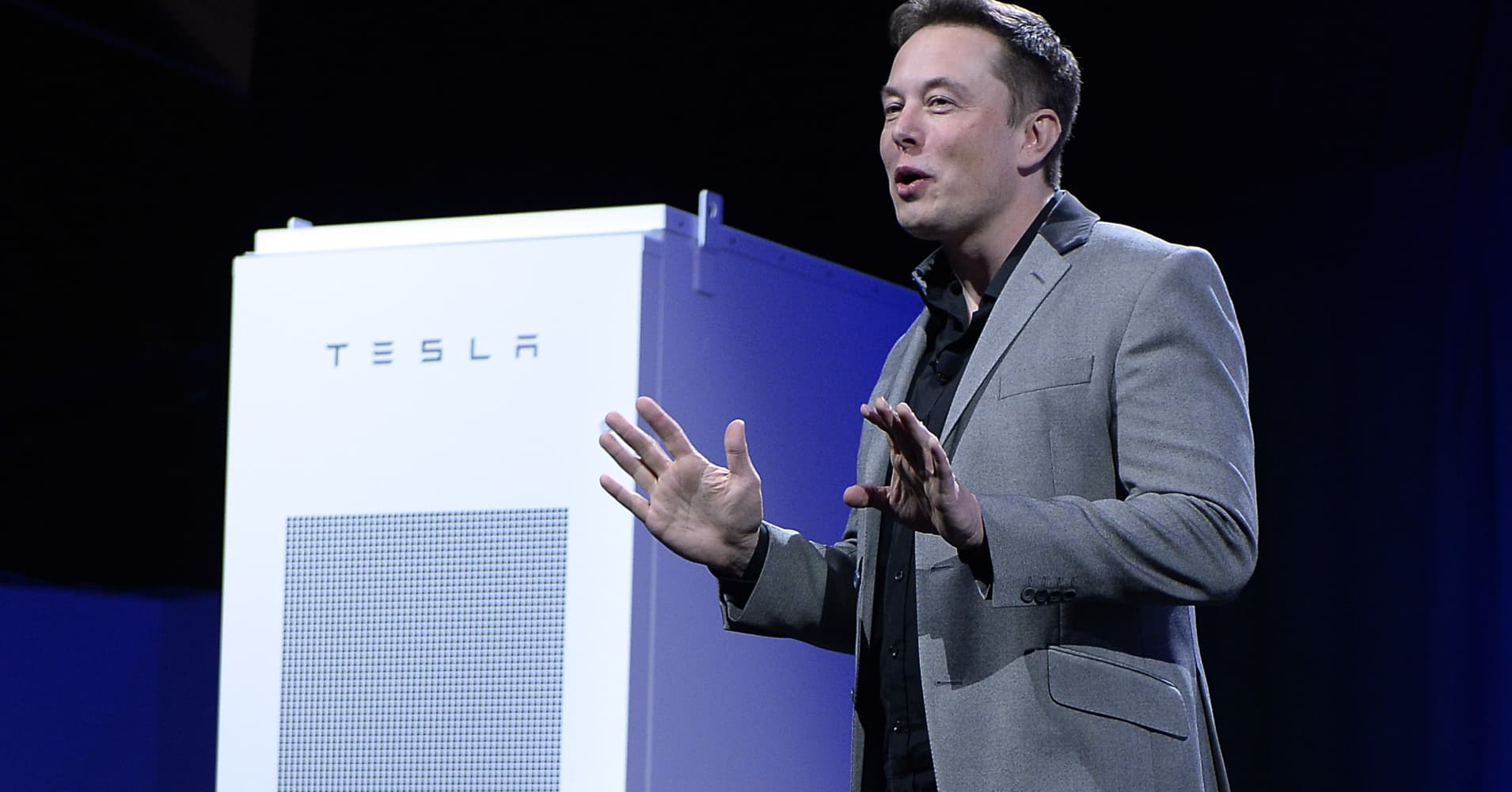 Elon Musk, CEO of Tesla, with a Powerpack unit the background unveils suit of batteries for homes, businesses, and utilities.