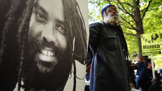 A protestor stands next to an image of Mumia Abu-Jamal outside the U.S. Department of Justice on April 24, 2012 in Washington.