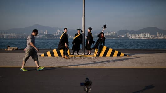 University students pose for graduation photographs on a public pier in Hong Kong.