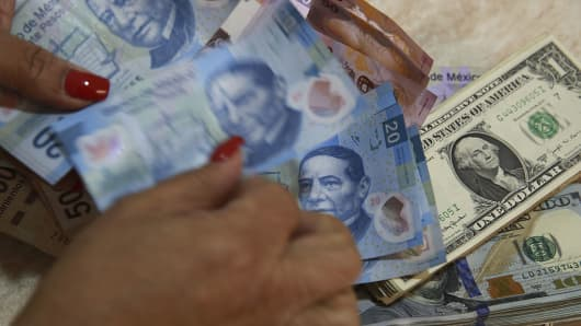 A Worker Counts Mexican Peso Bills On Top Of U S Dollar At Currency Exchange