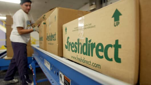 A worker shepherds finished grocery boxes ready for delivery at the new FreshDirect online grocery service warehouse in New York City.