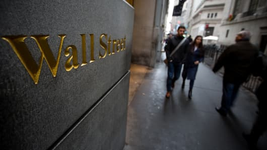 Pedestrians walk along Wall Street across from the New York Stock Exchange.