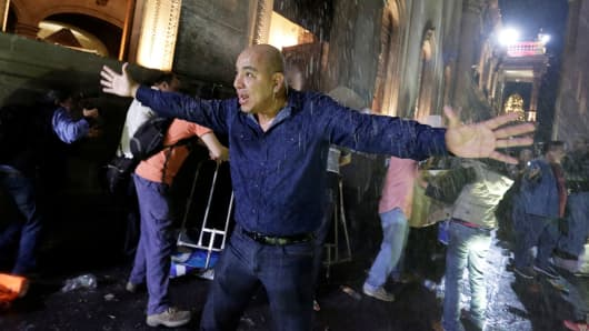 A man urges fellow demonstrators to calm down as they vandalize the Government Palace during a protest against the rising prices of gasoline, at the Macroplaza in Monterrey, Mexico, January 5, 2017.