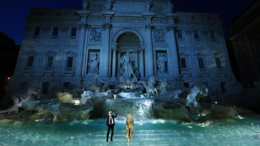 Karl Lagerfeld and Silvia Venturini Fendi acknowledge the applause of the public after the Fendi Roma 90 Years Anniversary fashion show at Fontana di Trevi on July 7, 2016