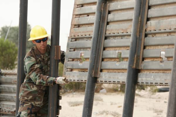A member of the 116th Construction Equipment Support Company of the Utah National Guard extends a wall along the US border with Mexico to prevent illegal immigration, a few miles from the border crossing point at San Luis, Arizona.