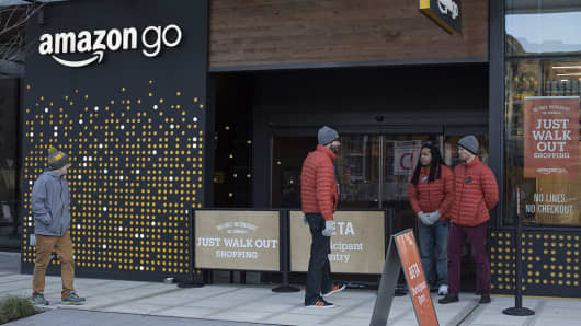 Employees stand outside the new Amazon Go grocery store in Seattle, Washington, U.S., on Tuesday, Dec. 6, 2016.