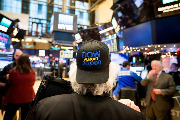 A trader wearing a 'DOW ALMOST 20,000' hat works on the floor of the New York Stock Exchange (NYSE) in New York.