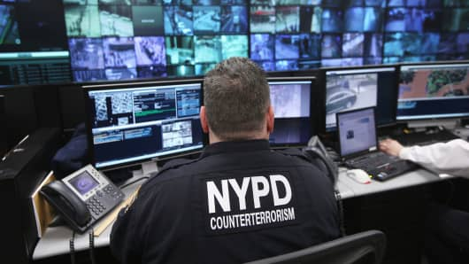 Police and private security personnel monitor security images in New York City.